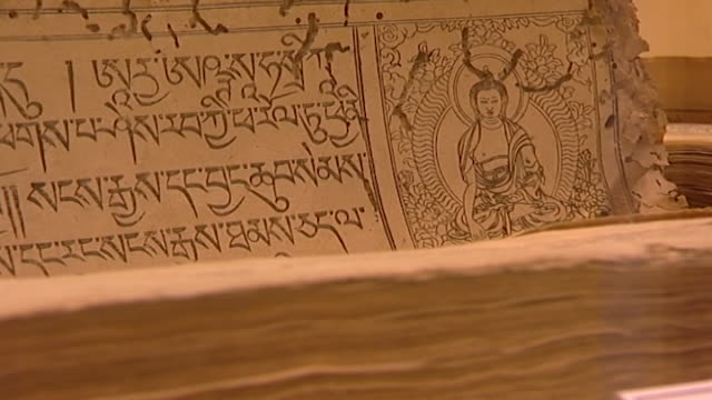 men-tsee-khang, dharamsala. a buddhist figure on an ancient medical manuscript written in tibetan in a glass casing at a tibetan medical museum. - china east asia stock videos & royalty-free footage