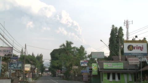stockvideo's en b-roll-footage met merapi volcano erupts at dawn visible from northern suburb of yogjakarta city; indonesia. 7 november 2010 / audio - 2010