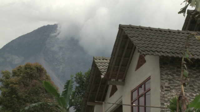 merapi volcano steams with house close by in foreground; central java, indonesia. 28 october 2010 - bedrohung stock-videos und b-roll-filmmaterial
