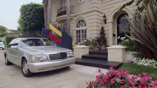 a mercedes sedan parks in the driveway of an upscale mansion. - ベンツ点の映像素材/bロール