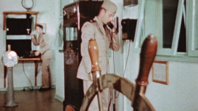 merchant marine checks an instrument panel and makes a phone call while another marine writes under supervision / alameda california united states - handhaben stock-videos und b-roll-filmmaterial