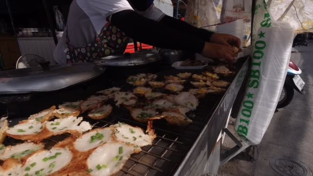merchant selling thai coconut rice cake at market - dessert topping stock videos & royalty-free footage