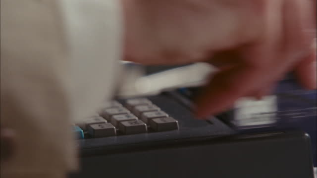 a merchant swipes a credit card through the reader several times. - punch card reader stock videos & royalty-free footage