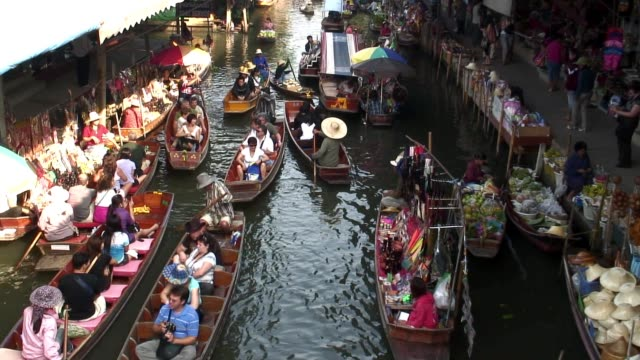Merchants sell goods along a floating market in Bangkok.