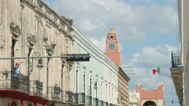 vídeos y material grabado en eventos de stock de merida mexico establishing shot. colonial style houses and city council building at the background with mexican national flag - colonial