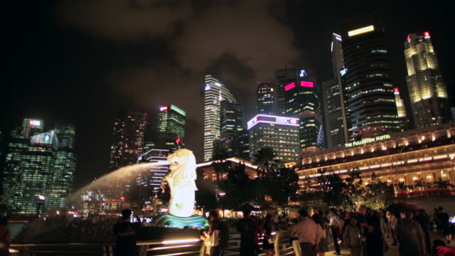 ws merlion statue and tourists with singapore city skyline - merlion fictional character stock videos and b-roll footage