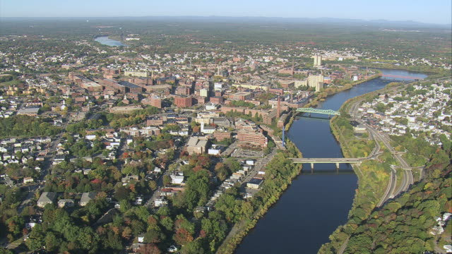 aerial merrimack river running through small city with downtown business district and old factories by the riverbank / lowell, massachusetts, united states - lowell stock videos & royalty-free footage