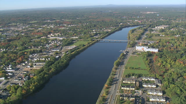 aerial merrimack river with the city lining both riverbanks and bridges crossing / lowell, massachusetts, united states - lowell stock videos & royalty-free footage