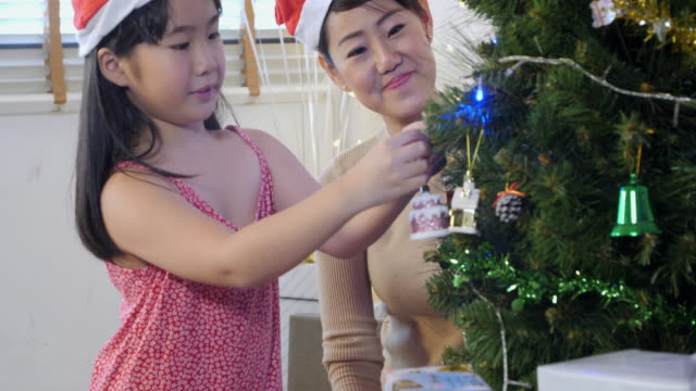 merry christmas and happy holidays! mom and daughter decorate the christmas tree indoors. the morning before xmas.christmas in hong kong - happy holidays stock videos & royalty-free footage