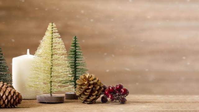 メリークリスマスと幸せな新年の背景とクリスマスツリーとヤシの葉と雪の秋と木製のテーブルに松のコーン. - パインコーン点の映像素材/bロール