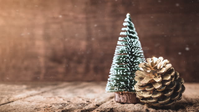 merry christmas and happy new year background.christmas tree and pine cone with snow falling on grunge wood table and dark brown wooden wall.winter holiday greeting card. - wood material stock videos & royalty-free footage