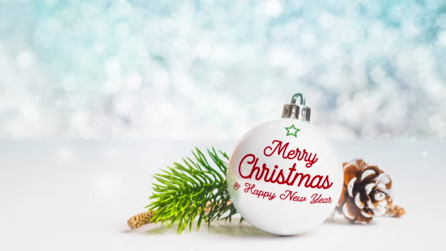 merry christmas and happy new year on white christmas glossy ball on white table at sparkling blue bokeh blur abstract background,holiday greeting seasonal - new year card stock videos & royalty-free footage