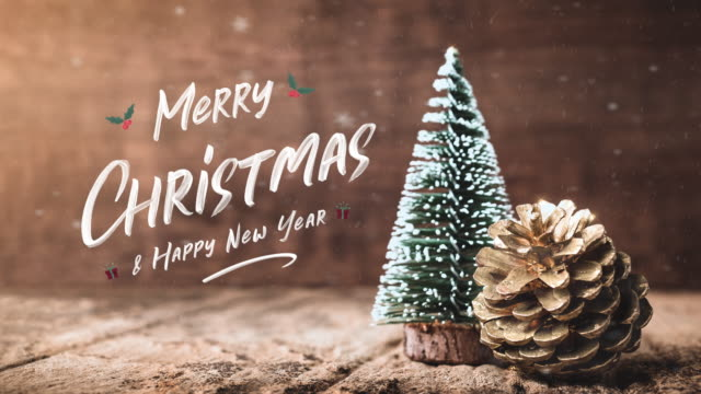 merry christmas and happy new year type floating at christmas tree and pine cone with snow falling on grunge wood table and dark brown wooden wall.winter holiday greeting card - legno video stock e b–roll