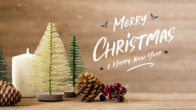 merry christmas and happy new year type floating at christmas tree and mistletoe leaf and pine cone on wooden table with snow fall.winter holiday seasonal greeting card - plank stock videos & royalty-free footage