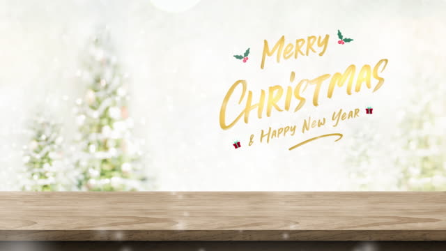 merry christmas and happy new year with mistletoe and gift box icon over wood table and snow falling with blur christmas tree bokeh light background,backdrop template for display of product or design. - template stock videos and b-roll footage