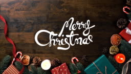 Merry Christmas greeting text appearing on wood table with beautiful decorating gift boxes