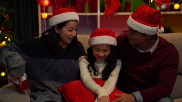 merry christmas! happy family mother father and daughter with magic gift near tree in living room - morning stock videos & royalty-free footage
