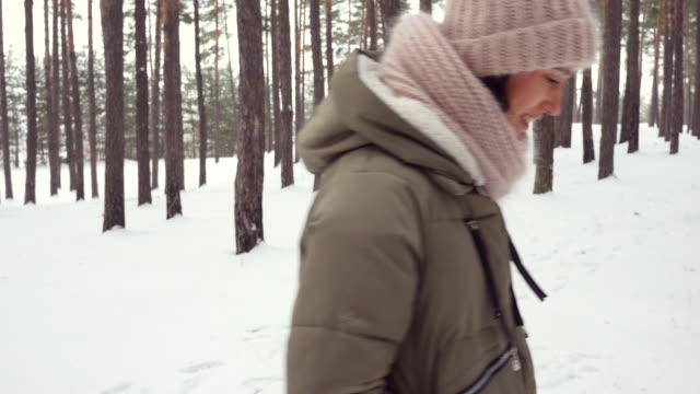 merry person having fun while strolling in the woods on winter day - mitten stock videos and b-roll footage
