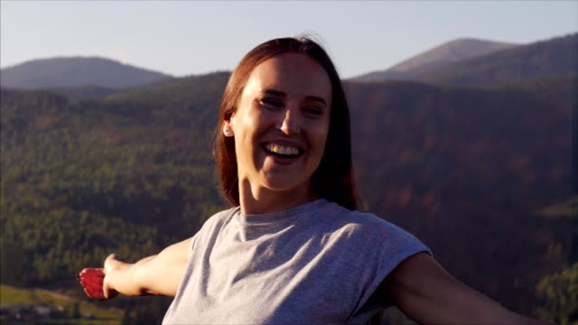 vidéos et rushes de femme joyeuse tendant les mains au coucher du soleil dans les montagnes - cheveux bruns