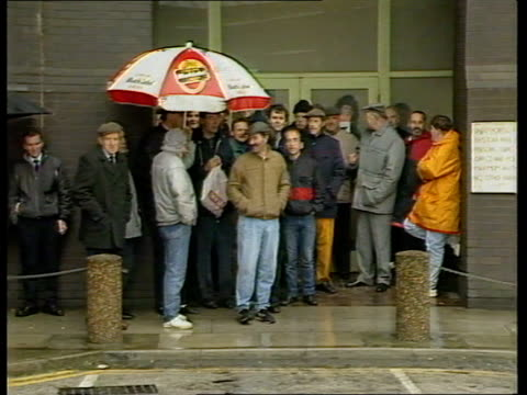merseyside: liverpool: ext / rain pickets standing on wall outside royal mail building pickets standing as chatting pickets as some under large... - ロイヤルメール点の映像素材/bロール