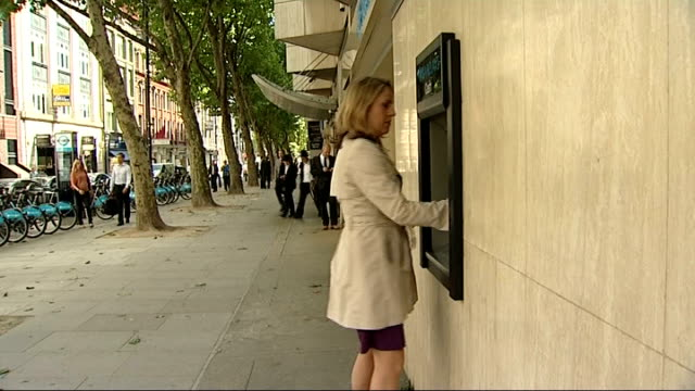 mervyn king criticises banking industry england london ext barclays sign tilt down reporter along to atm hand putting credit card into slot hand... - banking sign stock videos & royalty-free footage