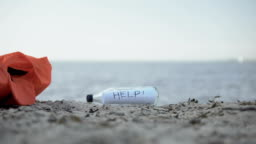Message Help in bottle lying on shore, concept of searching survivors of crashes