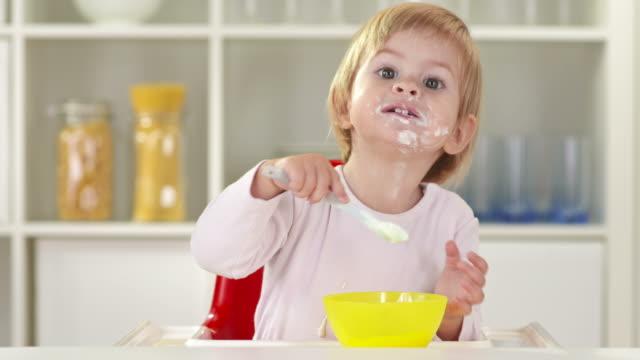 vídeos de stock e filmes b-roll de hd: desarrumado bebê menina comer na cadeira alta - amontoar