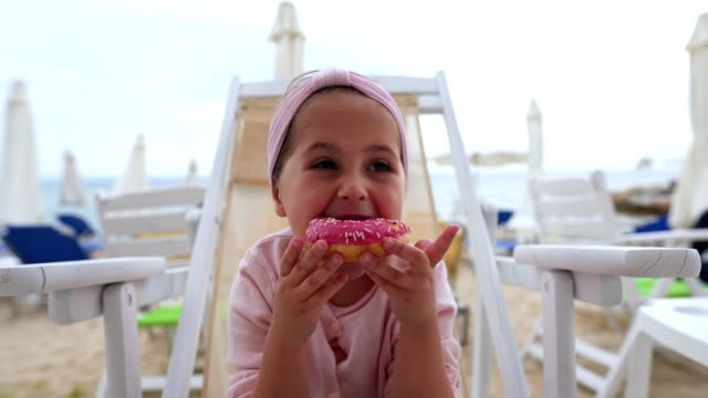messy child eating a strawberry donut on the beach - doughnut stock videos & royalty-free footage