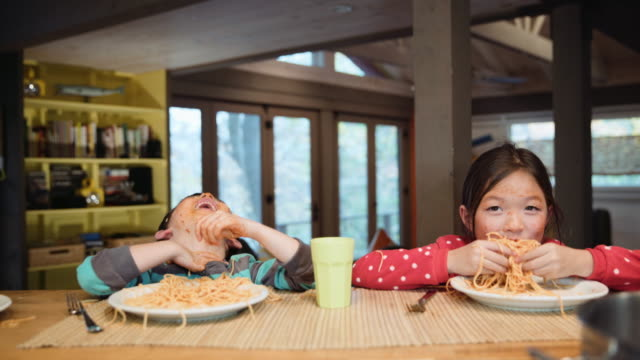 messy mixed race brother and sister eating spaghetti - unfug stock-videos und b-roll-filmmaterial