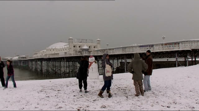 vídeos y material grabado en eventos de stock de met office issues new weather warning 2009 brighton ext people making snowman on beach location unknown cars along on snow covered road and people... - east sussex