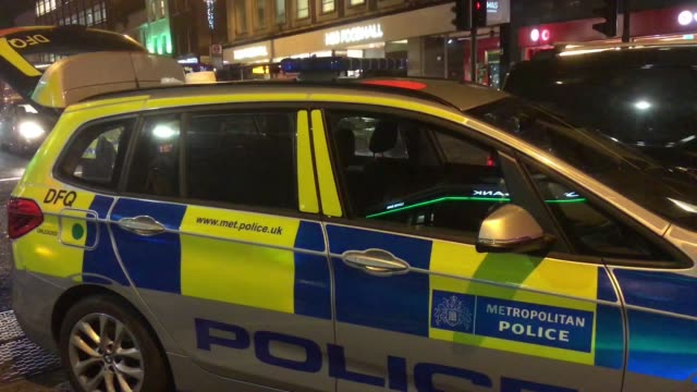 A Met Police Car with its emergency blue lights flashing attends a scene of a motoring accident in Camden Town London