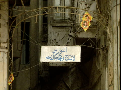 metal archway with arabic sign, crumbling buildings and two small images of saddam hussein in background / baghdad, iraq - male likeness stock videos & royalty-free footage
