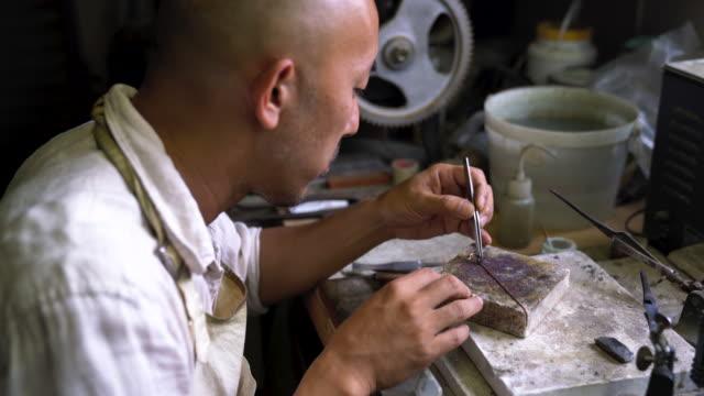 a metal artist working on a piece of handmade jewellery - craft点の映像素材/bロール