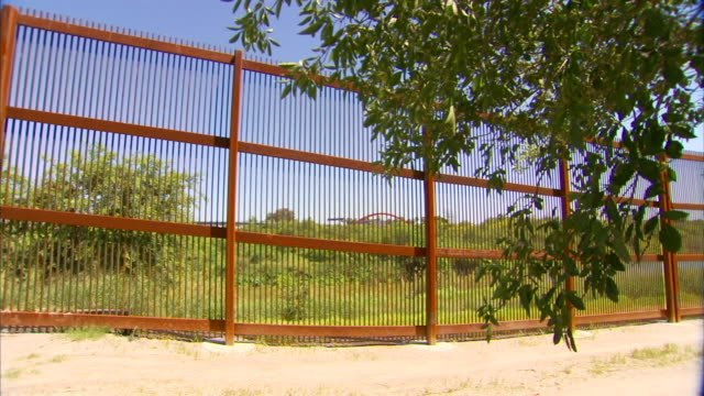 metal bars of mexicounited states border wall grass trees around partial red arches of gateway international bridge on matamoros side in distant bg... - international border stock videos and b-roll footage