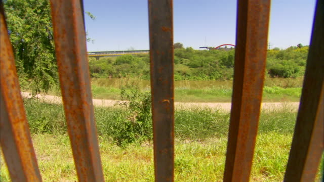 metal bars of mexico-united states border wall, grass, trees & dirt road bg, & gateway international bridge distant bg, to long wall along path. tx,... - international border stock videos & royalty-free footage