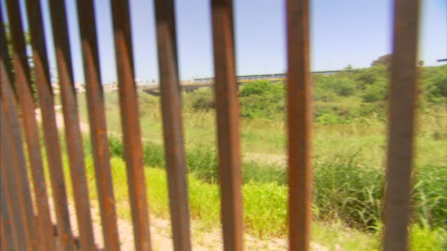 metal bars of mexico-united states border wall, grass, trees & gateway international bridge distant bg. tx, illegal aliens, immigration, drug trade,... - international border stock videos & royalty-free footage