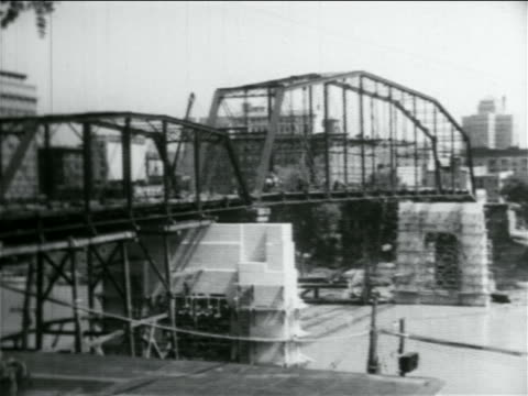 b/w 1934 metal bridge under construction over river / documentary - 1934 stock videos & royalty-free footage