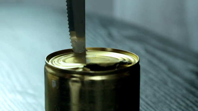 a metal can with condensed milk is opened with a knife. - condensed milk stock videos & royalty-free footage