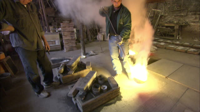 vídeos de stock e filmes b-roll de a metal caster fills molds with molten metal from a furnace at a foundry. - concha utensílio de servir