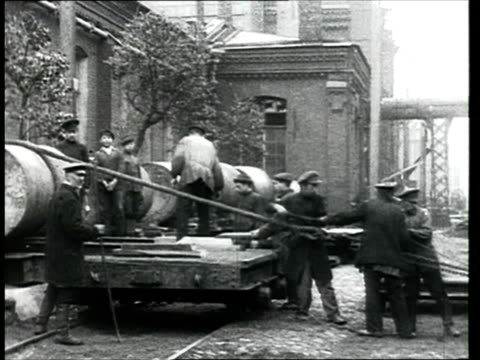 1914 montage b/w ws pan metal factory workers hoisting cylinders onto cart on street outside factory/ russia - 1914 stock videos & royalty-free footage