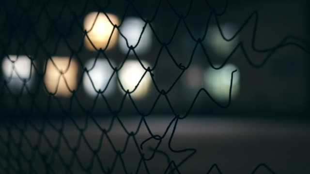 metal fence, lights in background - chainlink fence stock videos and b-roll footage