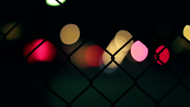 metal fence, lights, traffic in the background - chainlink fence stock videos and b-roll footage