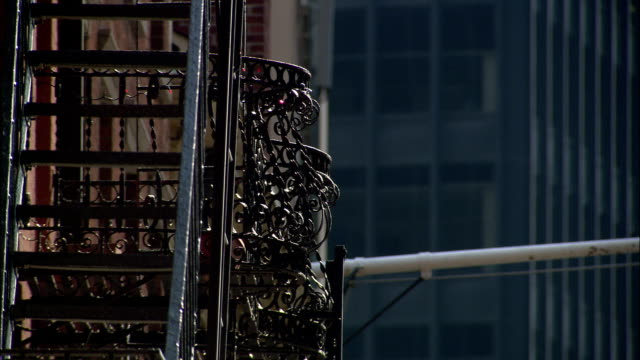 a metal fire escape extends up the side of a building. - fire escape stock videos and b-roll footage