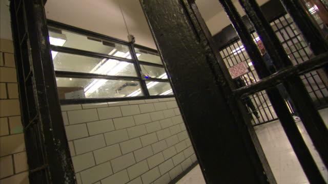 vidéos et rushes de a metal gate opens in a prison, and a man walks through. - porte structure créée par l'homme
