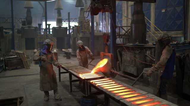 vídeos de stock, filmes e b-roll de trabalho da indústria metal - derramando metal derretido - linha de produção
