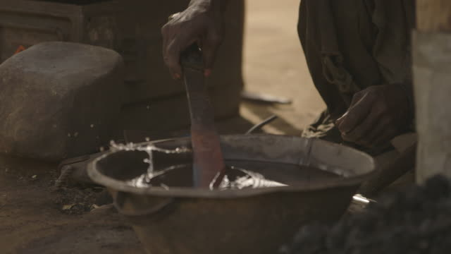 vídeos de stock e filmes b-roll de metal is hammered and heated tools are dipped into a bowl of water at a workshop in sierra leone. - ferro metal