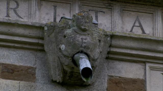 vídeos y material grabado en eventos de stock de a metal pipe protrudes from the chest of a gargoyle at rushton triangular lodge in northamptonshire, england. available in hd. - northamptonshire