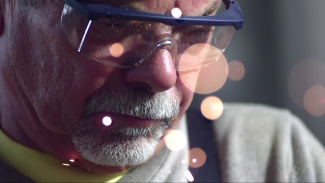 SLO MO Metal processing worker with safety glasses at work
