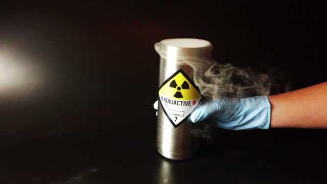 a metal radioactive canister with smoke being picked up by a hand in rubber glove - weapons of mass destruction stock videos & royalty-free footage