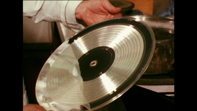 metal record 'stamper' being created in a factory; 1973 - film montage stock videos & royalty-free footage